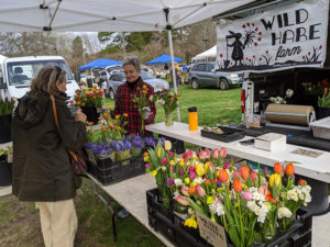 """Farmer Leah Cook of Wild Hare Farm demonstrates what she calls the market's new """"purchasing in a pandemic"""" policy as she has customers point to what they want so that she can pull the order together."""